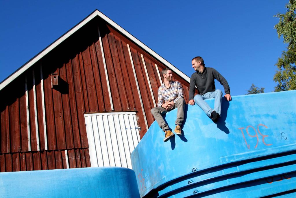 Gårdsfisk, fr v: Johan och Mikael på en stapel fiskbassänger utanför gården.
